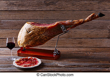 Iberian ham pata negra from Spain with red wine on wood...