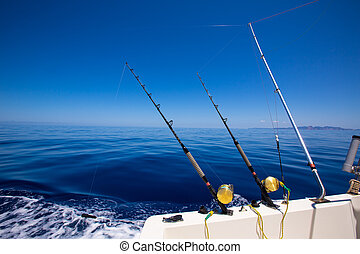 Ibiza fishing boat trolling rods and reels in blue sea -...