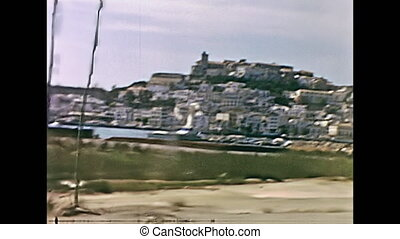 Historical restored driveby cityscape of Ivissa port town of Ibiza in seventies. The old harbour and the ancient Catedral de Santa Maria church on the top horizon. Spain on circa 1973.