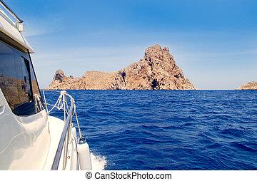 Ibiza yacht reaching Es Vedra island in Mediterranean blue...