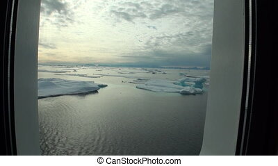 Ice and iceberg from porthole window of yacht in Arctic...