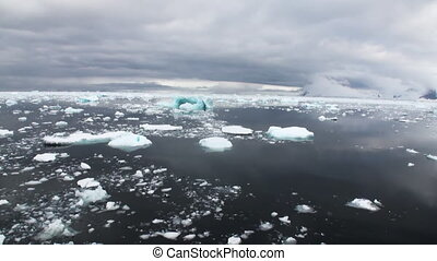 Ice and small icebergs floats on ocean surface.