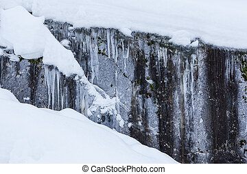 ice and snow covered rock cliff