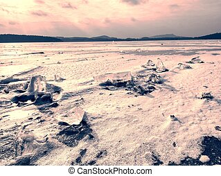 Ice breaking in pure nature. View over frozen water lake with sunset