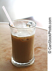 Cup of iced milk coffee in glass with straw