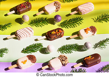 Ice cream and christmas decor on bright striped background.