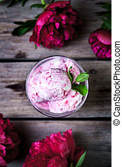 ice cream and peony flower as symbol of summer and holiday on wood background
