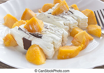 Ice cream cake with peach slices in plate