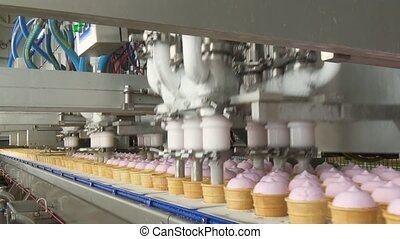 Ice cream factory. Filling of wafer cups with ice cream. Pink fruity and vanilla ice cream in a waffle cup. Automated production of ice cream.