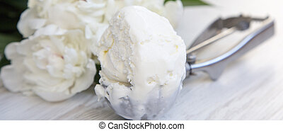 Ice cream in ice cream scoop with white peony blossom flowers on white wooden surface, close-up. Side view.