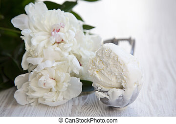 Ice cream in ice cream scoop with white peony blossom flowers over white wooden background, close-up.