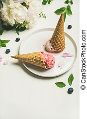 Ice cream scoops and peonies over white background, copy space