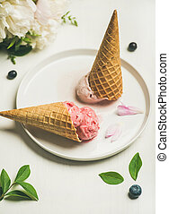 Ice cream scoops and peonies over white background, selective focus