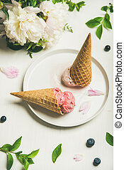Ice cream scoops and peony flowers over white background