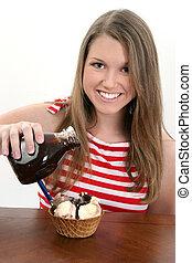 Ice Cream Sundae - Young teen girl pouring chocolate sauce...