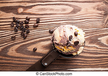 Ice cream with a spoon on a wooden board.