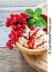 Ice cream with berry topping in a wooden bowl.