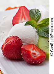 Ice cream dessert with strawberries and kiwi on a white table.