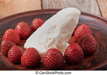 Ice cream with strawberries on an old wooden background.