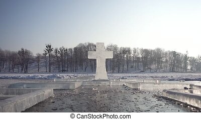 Sunny day shot of frozen ice cross sculpture on winter lake