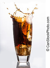 Ice cube falling into a glass of soda on white background