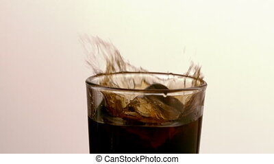 Ice cube falling into glass of sod - Ice cube falling into...