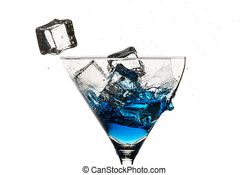 Ice cubes and broken martini glass with blue liqueur on white background