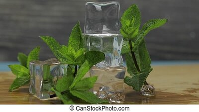 Ice cubes and mint leaves isolated on wooden cutting board -...