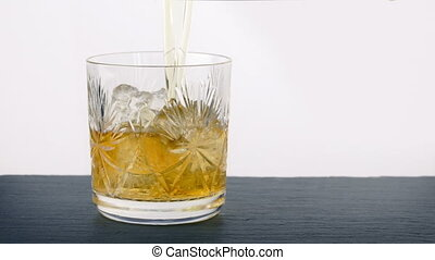 Ice Cubes And Whiskey Poured Into Glass - Ice cubes and...