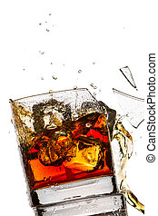 Ice cubes breaking whisky glass filled with bourbon on white...