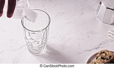 Hand puts fresh cubes of ice in a glass on a light grey marble background. Slow motion, Full HD video, 240fps, 1080p.