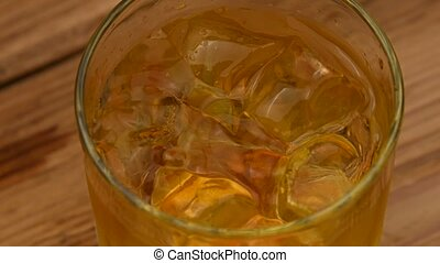 Ice cubes fall in glass of whiskey on bar counter
