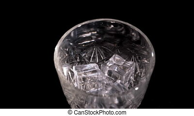 Ice cubes fall into a glass