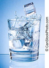 Ice cubes fall into glass of water on a blue background