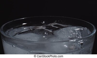 Ice cubes falling into a glass of water in slow motion.