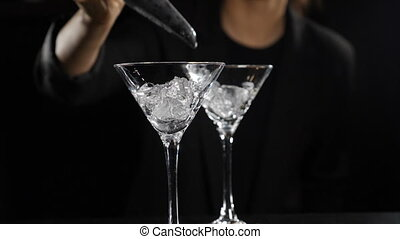 Ice cubes falling into empty glass in slow motion. Close up. Female bartender making cocktails on dark background. Nightclub and bar concept. Full hd