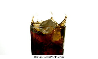 Ice cubes falling into glass of soda in slow motion