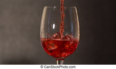 Ice cubes melting in glass of red drink. - Ice cubes melting...