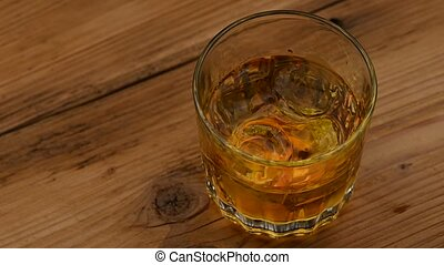 Ice cubes spin in glass of whiskey on table