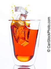 ice drop to glass of orange water