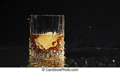 Ice dropped into glass of whisky splashing in slow motion...
