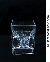 ice falling in a glass of water
