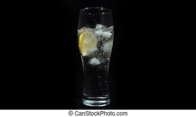 ice falls into a glass of mineral water and lemon, slow motion