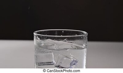 Ice falls into a glass of water.