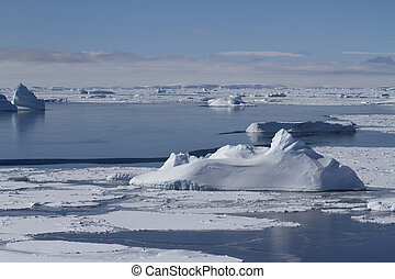 ice field and many small icebergs in the strait near the Anatrctic peninsula on a spring day