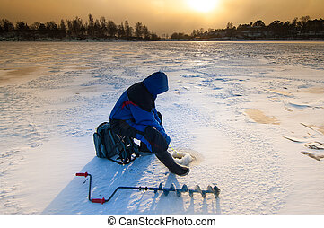 Ice fisher with ice auger - Ice fishing on thick ice with...