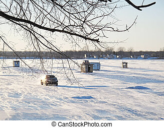 Ice fishermen's shelters on frozen lake in winter