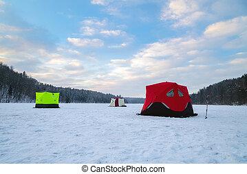 Ice fishing tent on a frozen lake at sunset. Fisherman camp on a peaceful winter evening.