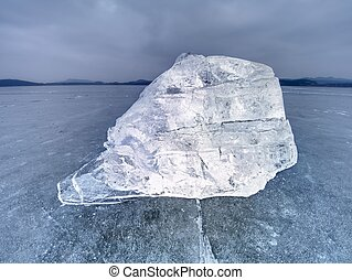 Ice floe and crushed ice on dark frozen and flat  ground. Shining crushed ice