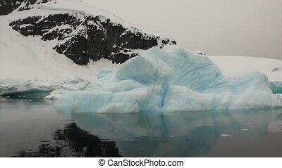 Ice floe and iceberg in ocean of Antarctica. Glacier on...